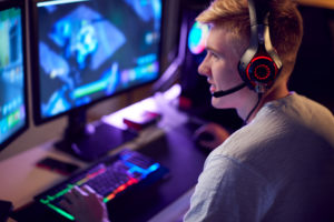 35016484-teenage-boy-wearing-headset-gaming-at-home-using-dual